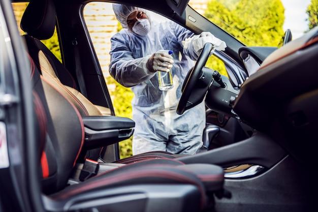 Mann im schutzanzug mit maske desinfiziert im auto, wischt saubere oberflächen ab, die häufig berührt werden, verhindert die infektion mit coronavirus, die kontamination von keimen oder bakterien. infektion