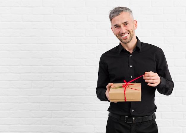 Mann im schwarzen anzug, der ein geschenk auspackt
