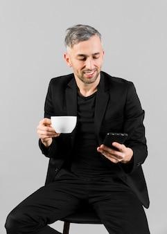 Mann im schwarzen anzug, der eine spindel hält und telefon betrachtet