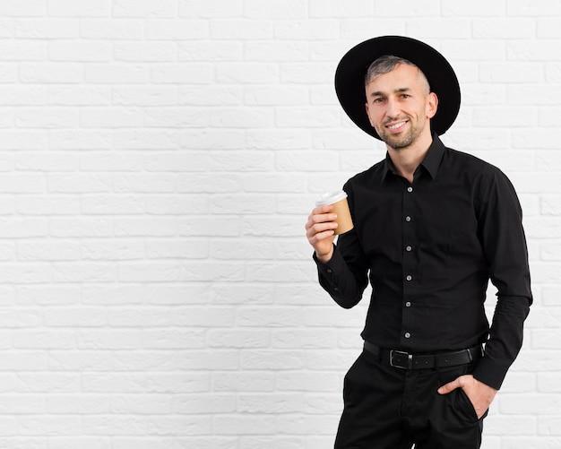 Mann im schwarzen anzug mit hut und hält kaffee