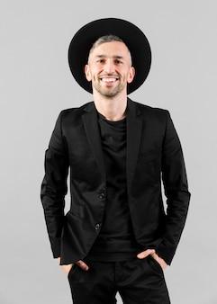 Mann im schwarzen anzug mit hut und händen in den taschen