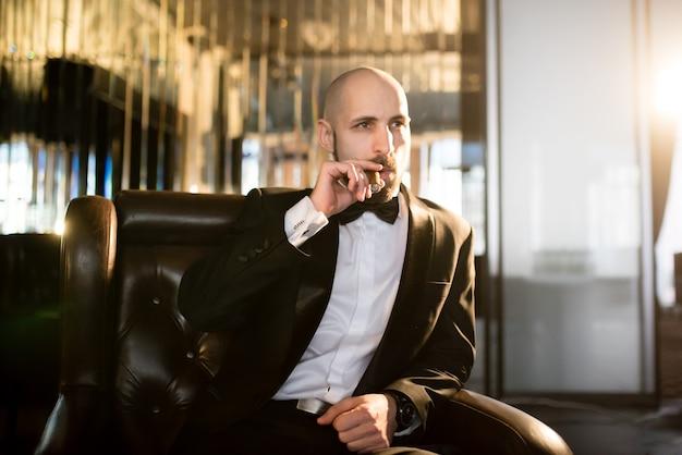Mann im schwarzen anzug raucht eine zigarre
