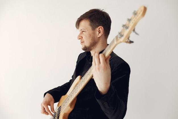 Mann im schwarzen anzug stehend mit einer gitarre
