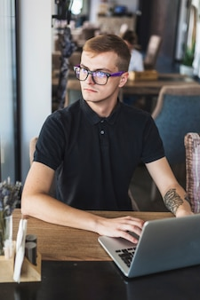 Mann im schwarzen, das an laptop im café arbeitet