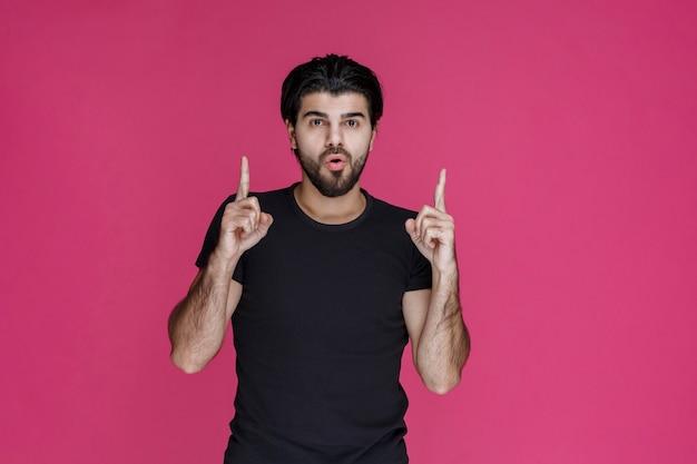 Mann im schwarzen hemd, das auf etwas zeigt oder jemanden vorstellt