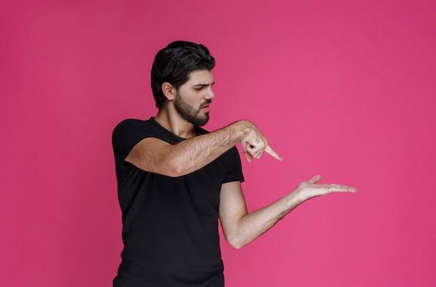 Mann im schwarzen hemd, das etwas in seiner hand zeigt