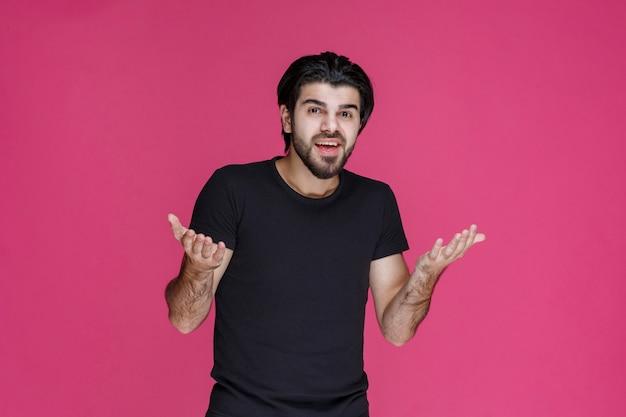 Mann im schwarzen hemd, das überraschend lächelt