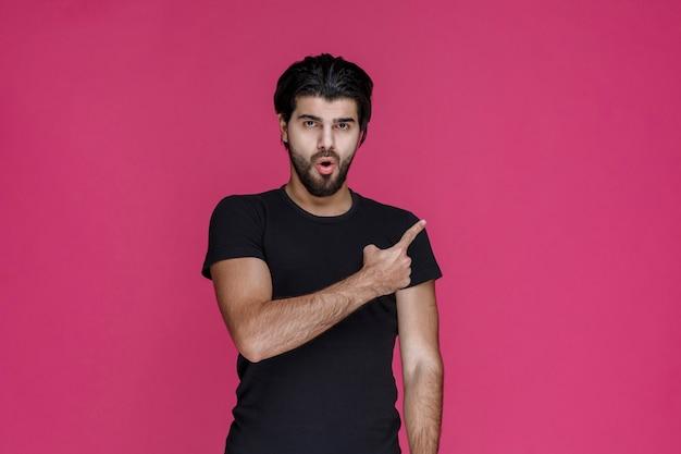 Mann im schwarzen hemd, der jemanden vorstellt und ihn zeigt