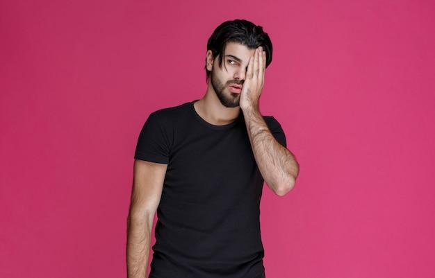 Mann im schwarzen hemd, der sein gesicht schließt, um sich zu verstecken