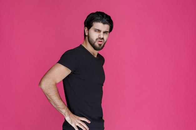Mann im schwarzen hemd, der sich über etwas negativ und enttäuscht fühlt