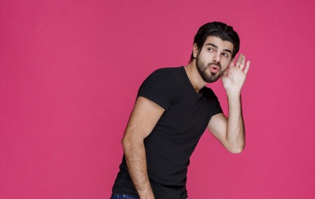 Mann im schwarzen hemd, der versucht, etwas zu hören