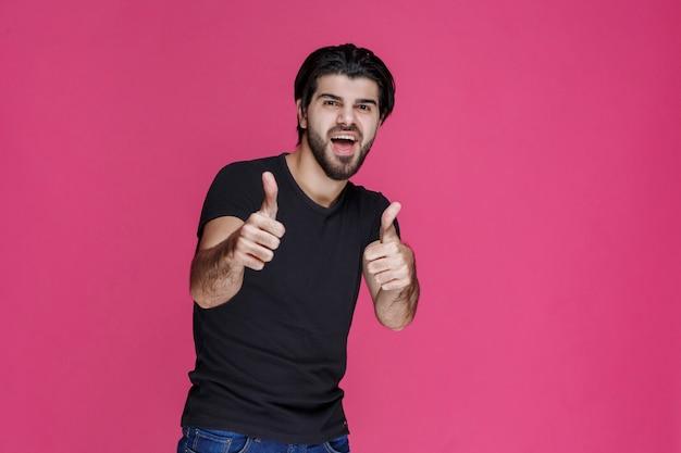Mann im schwarzen hemd fühlt sich über etwas positiv und genießt es