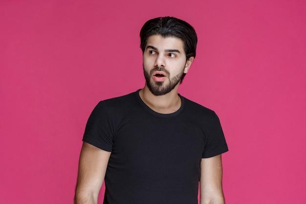 Mann im schwarzen hemd sieht nachdenklich, verwirrt und zögernd aus.