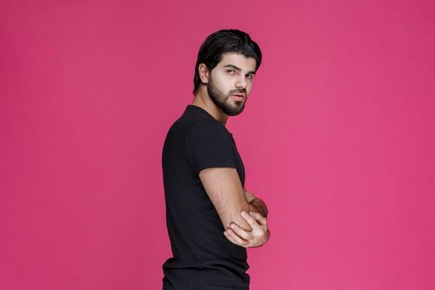 Mann im schwarzen hemd sieht selbstbewusst und kokett aus