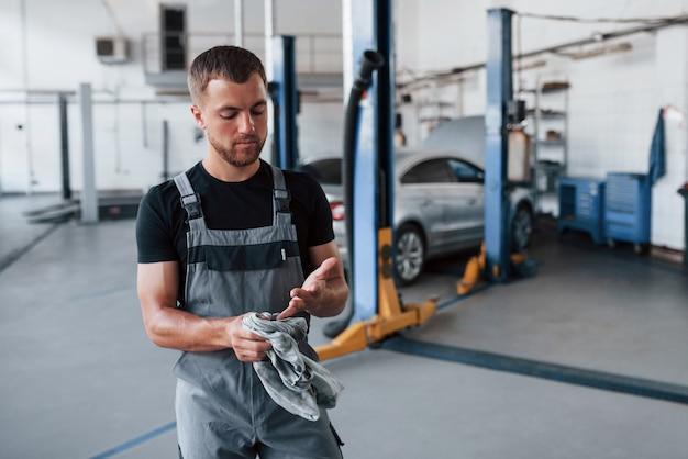 Mann im schwarzen hemd und in der grauen uniform steht in der garage, nachdem kaputtes auto repariert wird