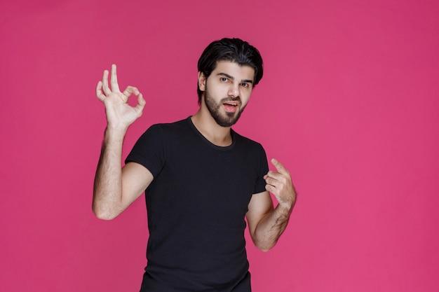 Mann im schwarzen hemd zeigt, dass er etwas völlig genießt