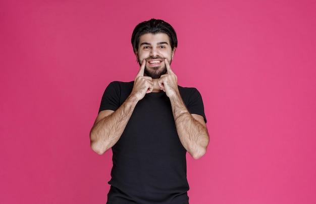 Mann im schwarzen hemd zeigt seinen mund und fragt lächelnd