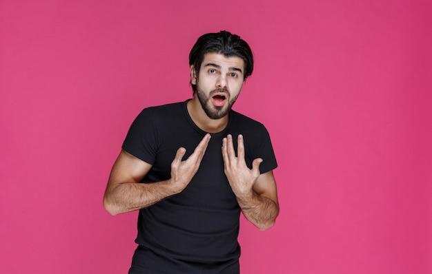 Mann im schwarzen hemd zeigt sich mit einer überraschenden und freudigen zuversicht
