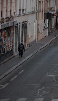 Mann im schwarzen mantel, der auf bürgersteig geht