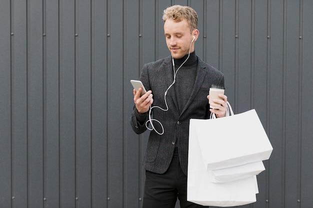 Mann im schwarzen mit dem kaffee, der smartphone betrachtet