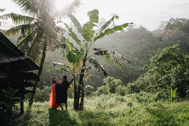 Mann im schwarzen regenmantel, der das gesicht der freundin auf natur berührt. paar touristen, die im regenwald aufwerfen.