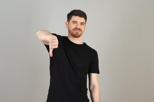 Mann im schwarzen t-shirt gestikuliert mit dem daumen nach unten auf einem grau.
