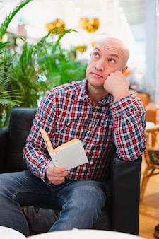 Mann im sitzen auf einem stuhl in einer hellen wohnung nachdenklich mit einem buch in seinen händen