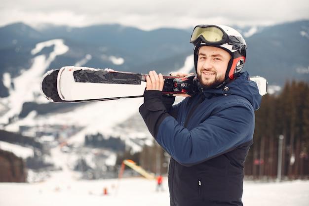 Mann im snowboardanzug. sportler auf einem berg mit einem snowboard in den händen am horizont. konzept zum sport