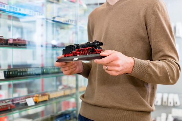 Mann im spielzeugladen, der modelleisenbahn kauft