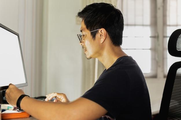 Mann im t-shirt, das am computer zu hause arbeitet.