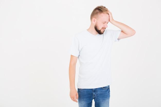 Mann im t-shirt, das unter kopfschmerzen leidet