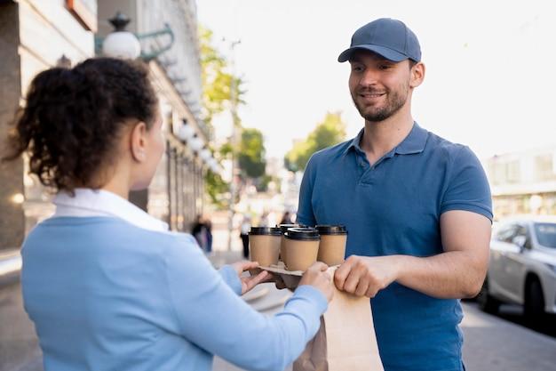 Mann im t-shirt, der essen zum mitnehmen liefert