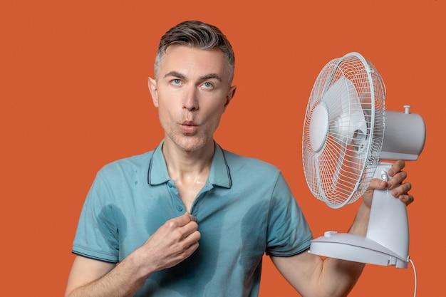 Mann im t-shirt mit nassen stellen mit ventilator