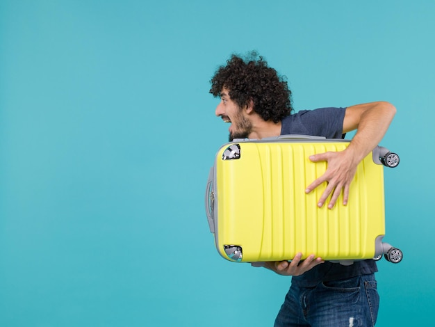 Mann im urlaub, der großen gelben koffer auf blau hält
