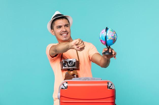 Mann im urlaub hält globus mit kamera auf blau