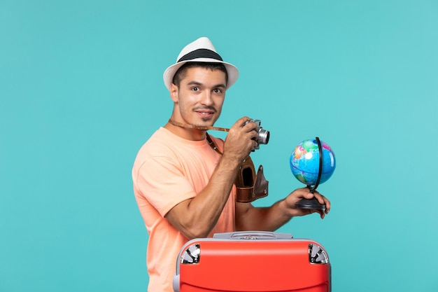 Mann im urlaub hält globus und macht fotos mit kamera auf blau