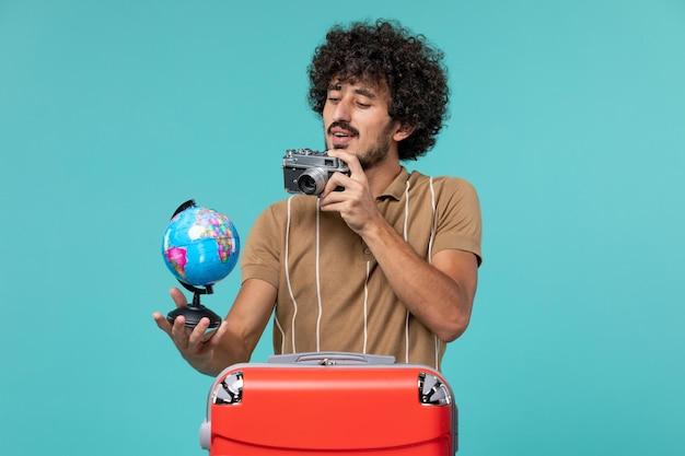 Mann im urlaub hält kleinen globus und kamera auf blau