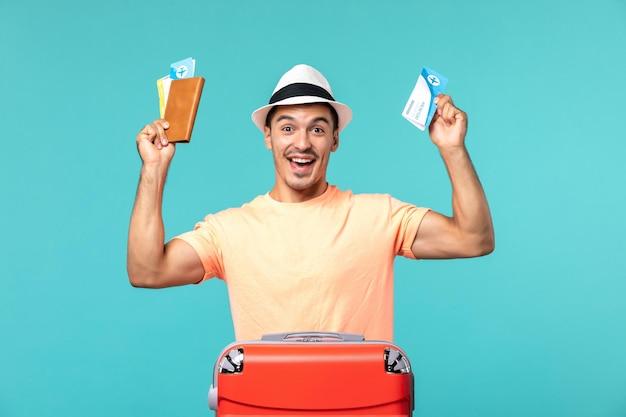 Mann im urlaub hält seine tickets und freut sich auf blau