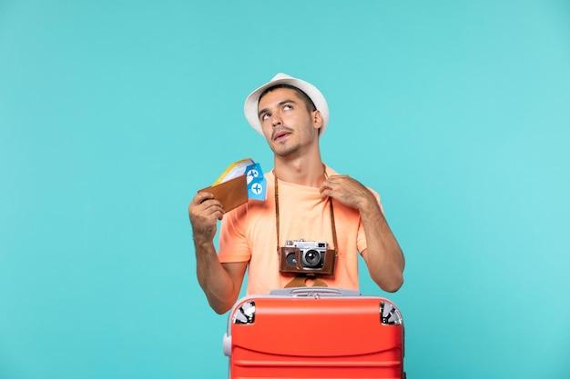 Mann im urlaub hält tickets mit roter tasche auf blau