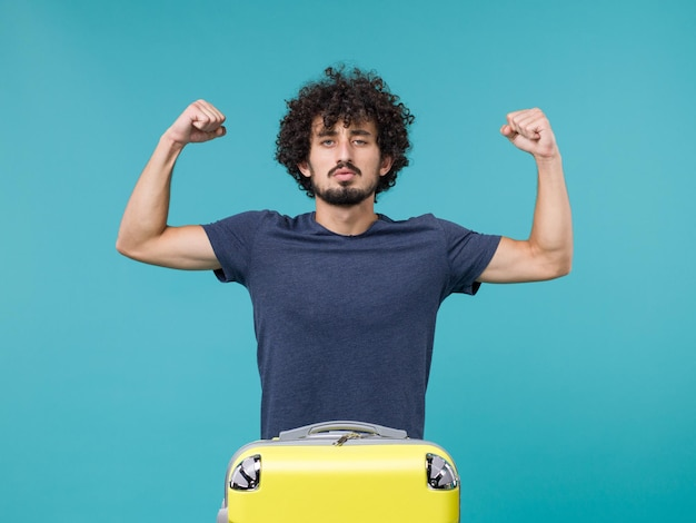 Mann im urlaub mit gelbem koffer, der sich auf blau biegt