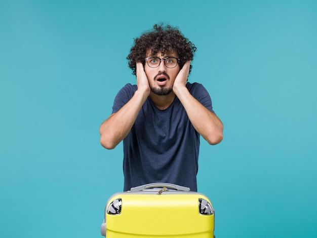 Mann im urlaub mit großem koffer auf blau