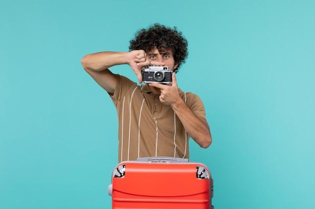 Mann im urlaub mit großem roten koffer, der fotos mit kamera auf blau macht
