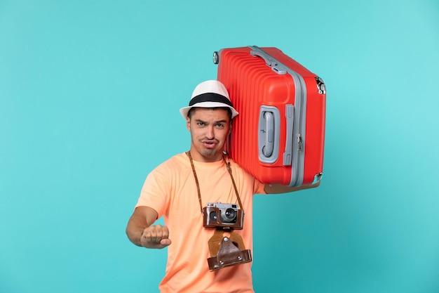 Mann im urlaub mit großen roten koffer auf blau Kostenlose Fotos
