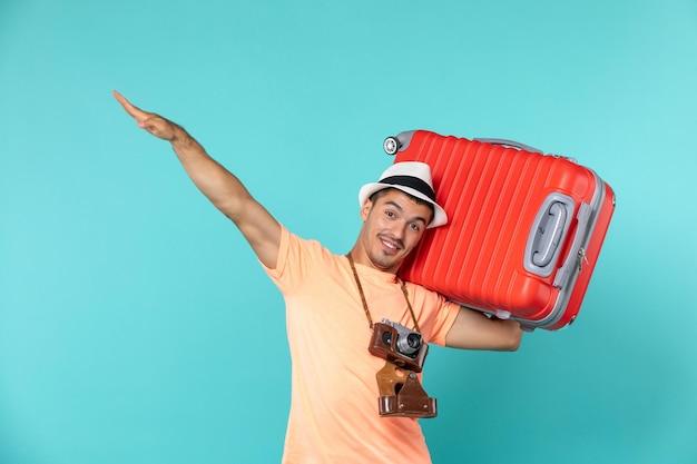 Mann im urlaub mit großen roten koffer auf blau