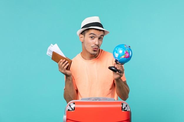 Mann im urlaub mit kleinen globus und tickets auf blau
