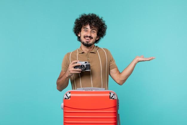 Mann im urlaub mit rotem koffer, der fotos mit der kamera auf hellblau macht