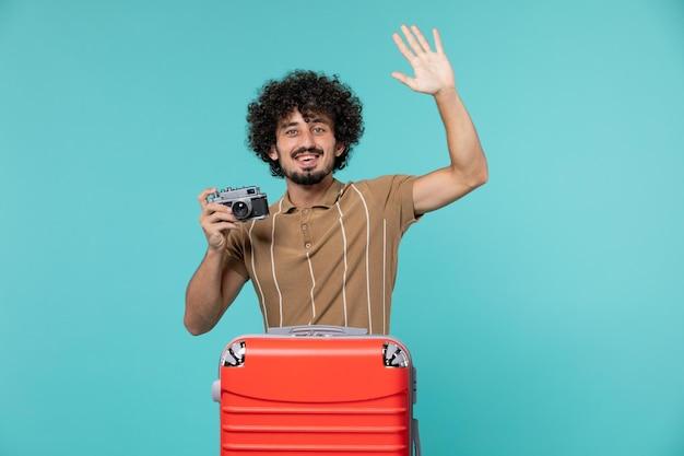 Mann im urlaub mit rotem koffer, der fotos mit kamera auf blau macht