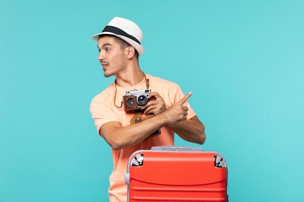 Mann im urlaub mit seinem großen roten koffer und seiner kamera, die fotos auf blau macht