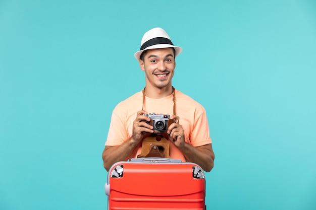 Mann im urlaub mit seinem roten koffer, der fotos mit der kamera auf blau macht