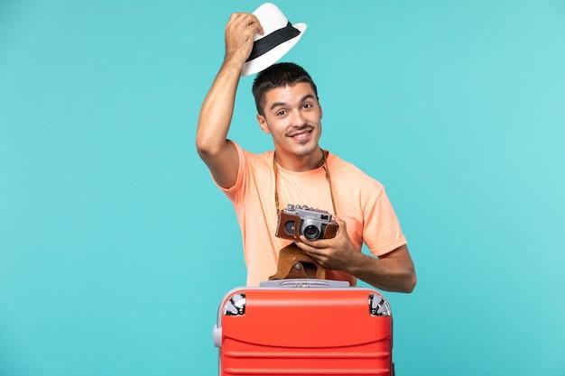 Mann im urlaub mit seinem roten koffer und kamera auf blau